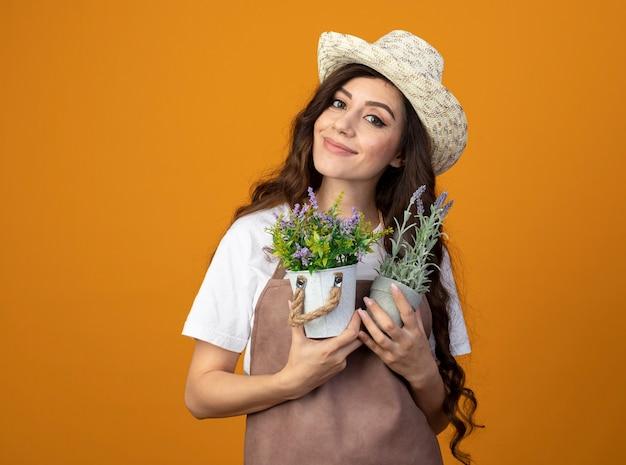 Jovem jardineira satisfeita em uniforme, usando um chapéu de jardinagem, segurando vasos de flores isolados na parede laranja com espaço de cópia