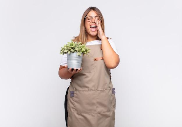 Jovem jardineira se sentindo feliz, animada e positiva, dando um grande grito com as mãos perto da boca, gritando