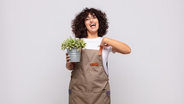 Jovem jardineira se sentindo feliz, surpresa e orgulhosa, apontando para si mesma com um olhar animado e surpreso