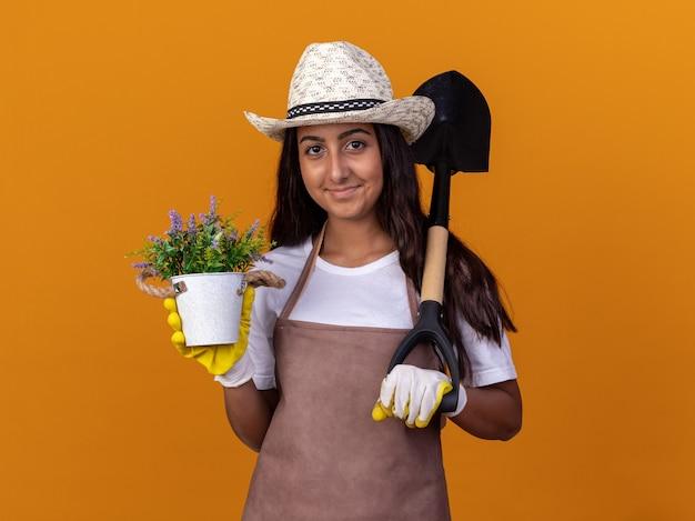 Jovem jardineira segurando uma planta em um vaso e uma pá com um sorriso no rosto em pé sobre a parede laranja