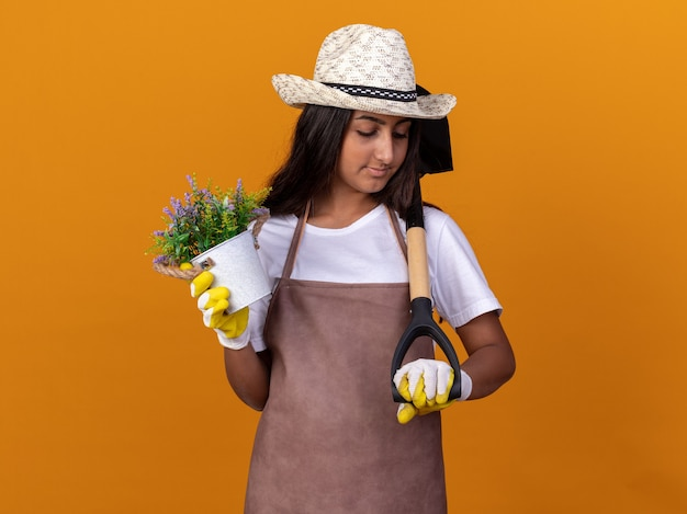 Jovem jardineira segurando uma planta em um vaso e uma pá, parecendo confiante em pé sobre a parede laranja