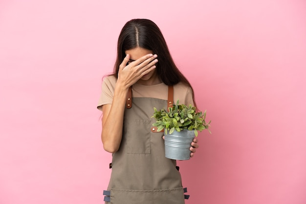 Jovem jardineira segurando uma planta isolada em um fundo rosa com expressão de cansaço e doentia