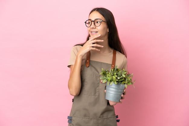 Jovem jardineira segurando uma planta isolada em um fundo rosa, olhando para cima enquanto sorri