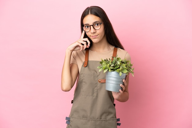 Jovem jardineira segurando uma planta isolada em um fundo rosa pensando em uma ideia