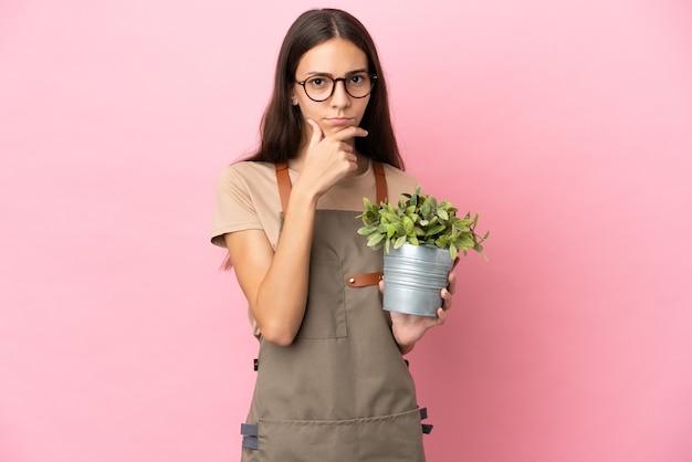 Jovem jardineira segurando uma planta isolada em um fundo rosa pensando
