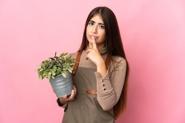 Jovem jardineira segurando uma planta isolada em um fundo rosa, tendo dúvidas enquanto olha para cima