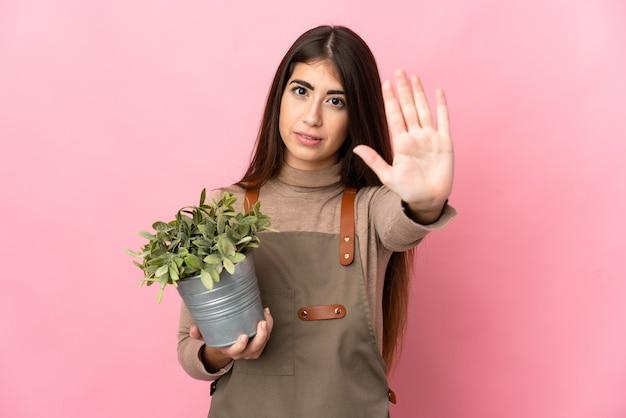 Jovem jardineira segurando uma planta isolada fazendo um gesto de parada