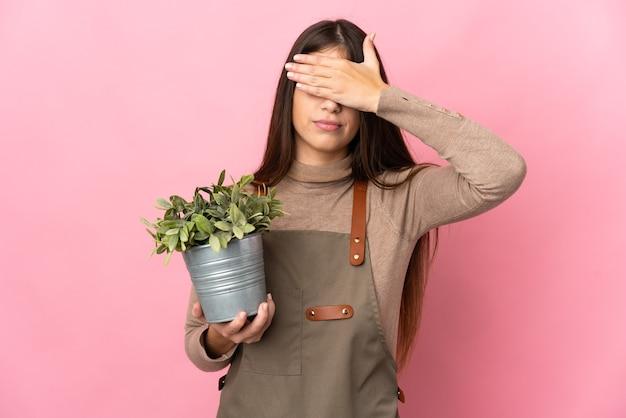 Jovem jardineira segurando uma planta isolada no fundo rosa, cobrindo os olhos com as mãos. não quero ver nada