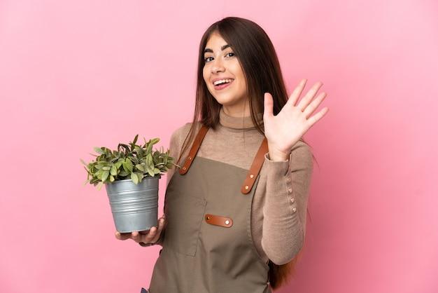 Jovem jardineira segurando uma planta isolada saudando com a mão com expressão feliz