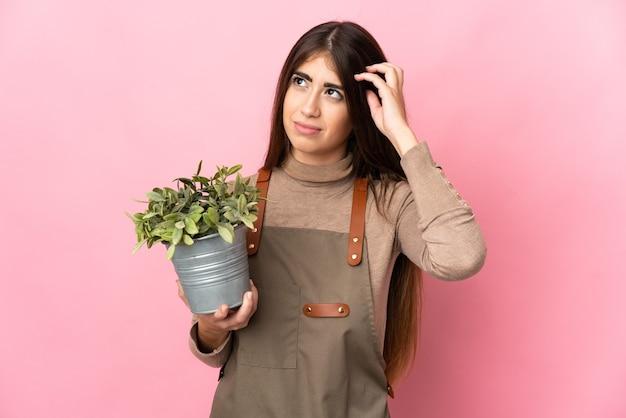 Jovem jardineira segurando uma planta isolada, tendo dúvidas