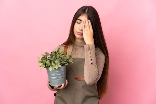Jovem jardineira segurando uma planta isolada