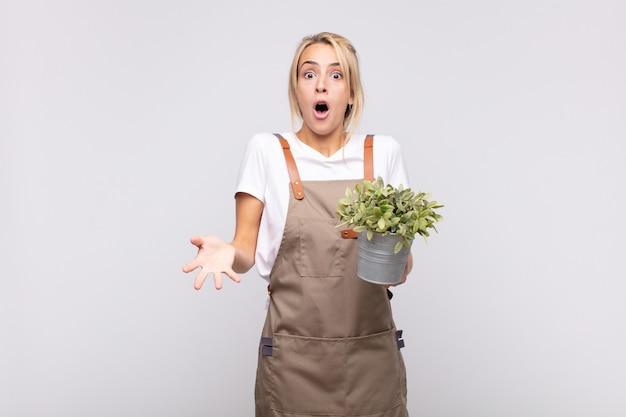 Jovem jardineira sentindo-se extremamente chocada e surpresa, ansiosa e em pânico, com um olhar estressado e horrorizado