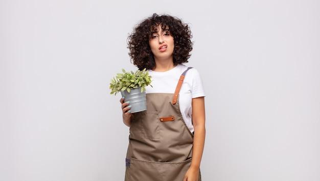 Jovem jardineira sentindo-se perplexa e confusa, com uma expressão muda e atordoada olhando para algo inesperado