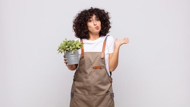 Jovem jardineira sentindo-se perplexa e confusa, duvidando, ponderando ou escolhendo diferentes opções com expressão engraçada