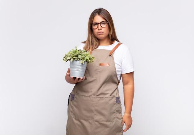 Jovem jardineira sentindo-se triste, chateada ou com raiva e olhando para o lado com uma atitude negativa, franzindo a testa em desacordo