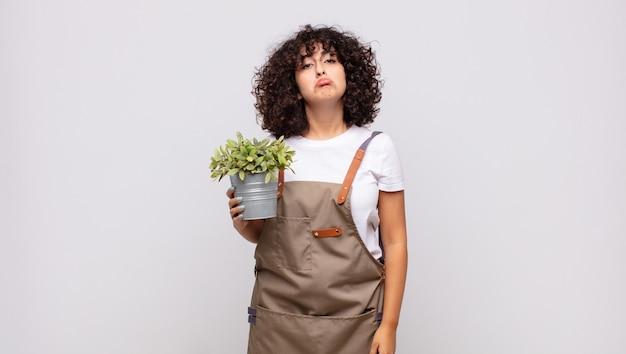 Jovem jardineira sentindo-se triste e chorona com uma expressão infeliz, chorando com uma atitude negativa e frustrada