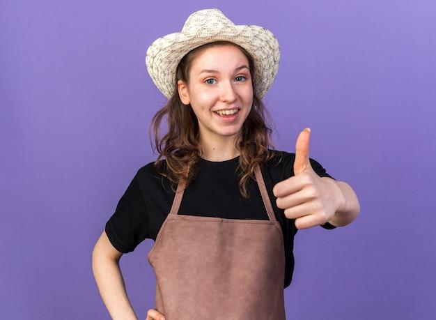 Jovem jardineira sorridente com chapéu de jardinagem aparecendo o polegar isolado na parede azul
