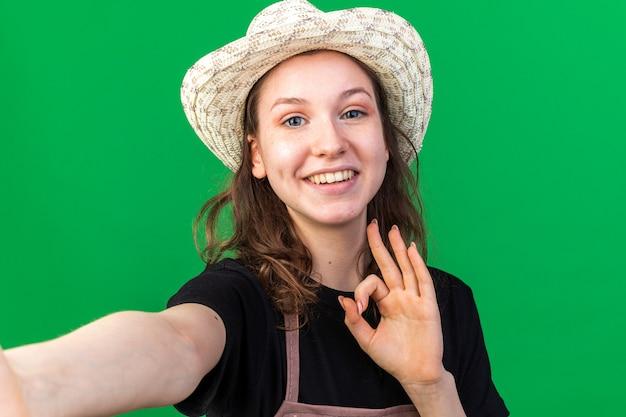Jovem jardineira sorridente com chapéu de jardinagem segurando mostrando gesto de ok isolado na parede verde