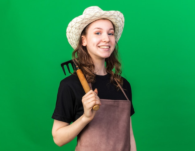 Jovem jardineira sorridente com chapéu de jardinagem segurando um ancinho no ombro