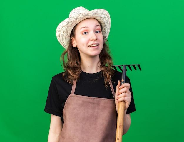 Jovem jardineira sorridente com chapéu de jardinagem segurando um ancinho