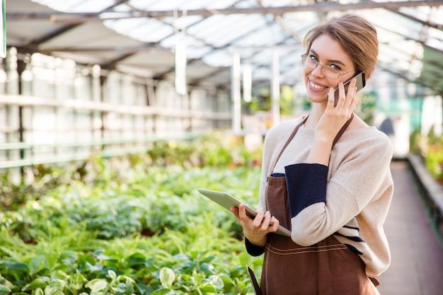 Jovem jardineira sorridente de uniforme e óculos usando celular e tablet em estufa