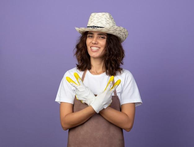 Jovem jardineira sorridente de uniforme usando chapéu de jardinagem e luvas, cruzando as mãos e mostrando um gesto de paz