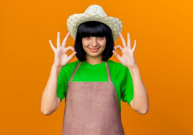 Jovem jardineira sorridente de uniforme usando chapéu de jardinagem gesticulando com a mão bem sinalizada
