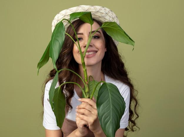 Jovem jardineira sorridente de uniforme usando chapéu de jardinagem segura a planta na frente do rosto, isolada na parede verde oliva