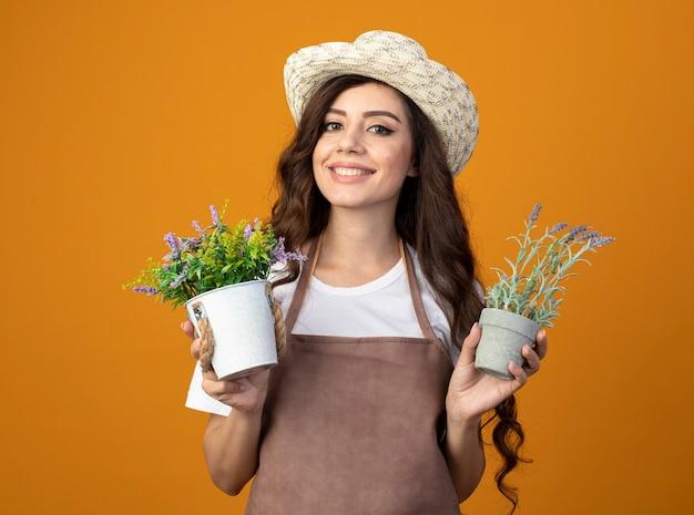Jovem jardineira sorridente de uniforme usando chapéu de jardinagem segura vasos de flores isolados na parede laranja com espaço de cópia
