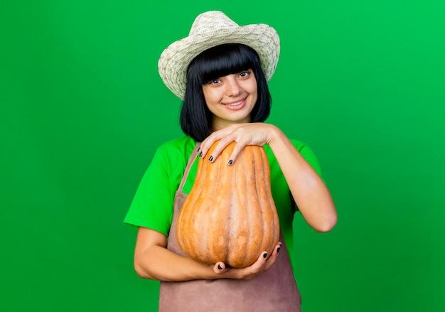Jovem jardineira sorridente de uniforme usando chapéu de jardinagem segurando abóbora olhando