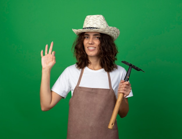 Jovem jardineira sorridente de uniforme usando chapéu de jardinagem segurando o ancinho mostrando um gesto de aprovação