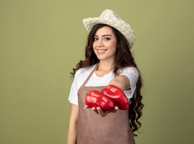 Jovem jardineira sorridente de uniforme usando chapéu de jardinagem segurando pimentas vermelhas isoladas na parede verde oliva