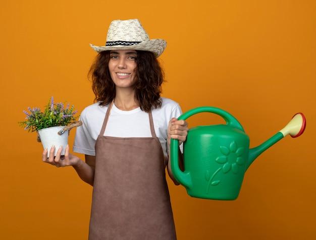 Jovem jardineira sorridente de uniforme usando chapéu de jardinagem segurando um regador com uma flor em um vaso isolado em laranja