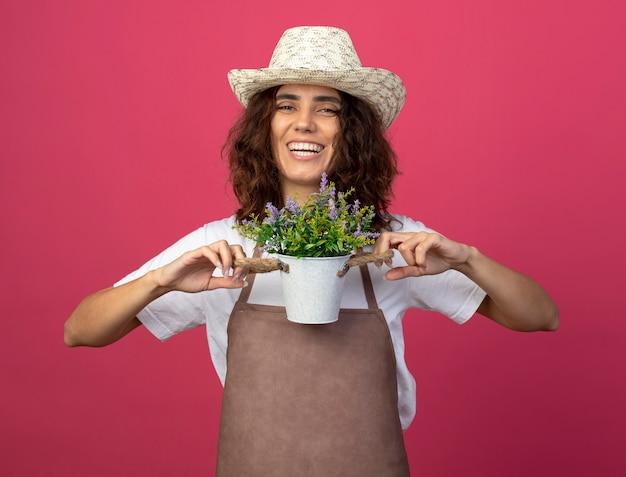 Jovem jardineira sorridente de uniforme usando chapéu de jardinagem segurando uma flor em um vaso isolado em rosa