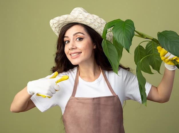 Jovem jardineira sorridente de uniforme usando luvas e chapéu de jardinagem segurando e apontando para uma planta isolada na parede verde oliva com espaço de cópia