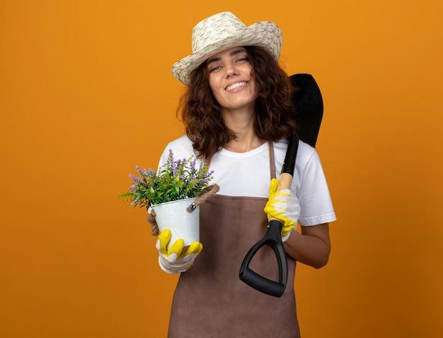 Jovem jardineira sorridente de uniforme usando luvas e chapéu de jardinagem, segurando uma flor em um vaso de flores e colocando a pá no ombro isolado em laranja