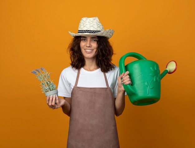 Jovem jardineira sorridente de uniforme, usando um chapéu de jardinagem, segurando uma flor em um vaso de flores com um regador