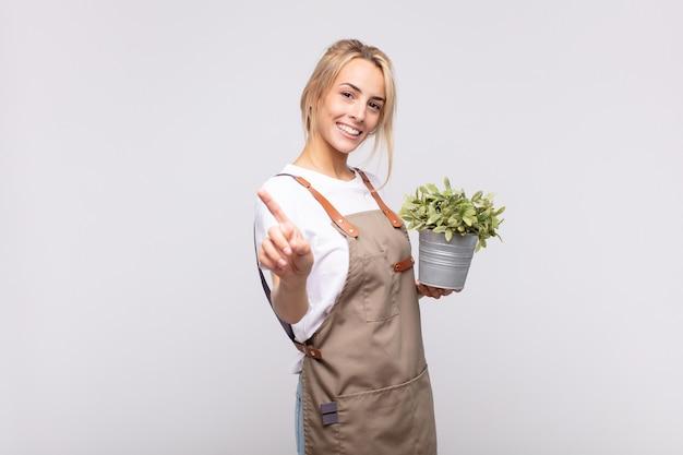 Jovem jardineira sorrindo com orgulho e confiança, fazendo a pose número um de forma triunfante, sentindo-se uma líder