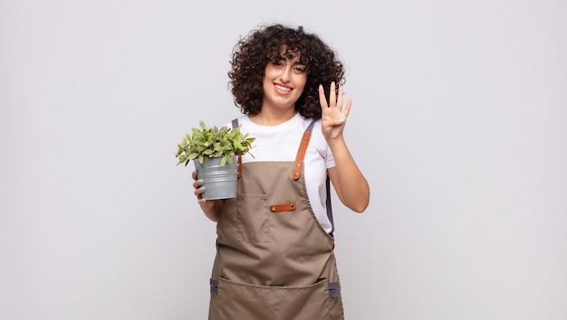 Jovem jardineira sorrindo e parecendo amigável, mostrando o número quatro ou o quarto com a mão para a frente, em contagem regressiva