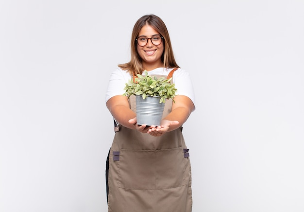 Jovem jardineira sorrindo feliz com um olhar amigável, confiante e positivo, oferecendo e mostrando um objeto ou conceito