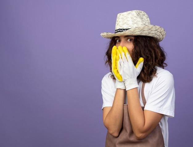 Jovem jardineira surpresa de uniforme, usando chapéu de jardinagem e luvas, cobrindo o rosto com as mãos