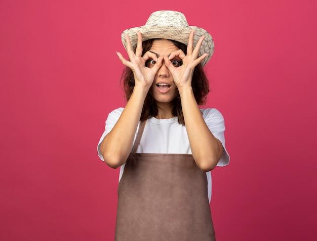 Jovem jardineira surpresa de uniforme usando chapéu de jardinagem, mostrando gesto de olhar