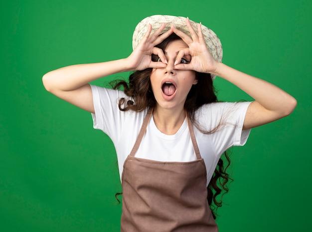 Jovem jardineira surpresa de uniforme, usando chapéu de jardinagem, olhando para a frente através dos dedos isolados na parede verde