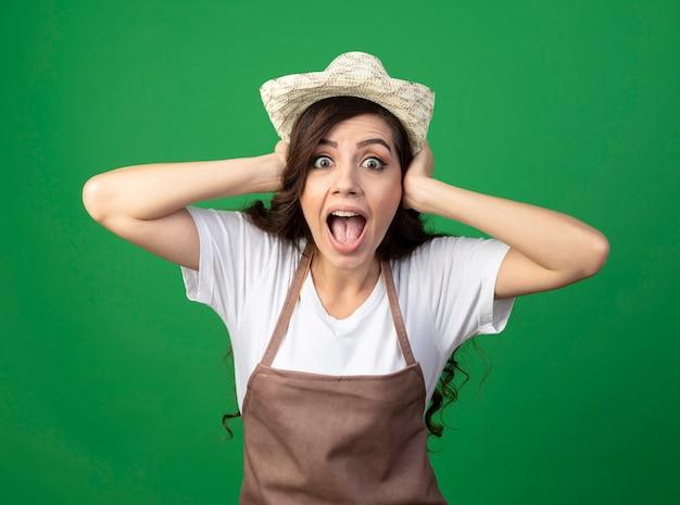 Jovem jardineira surpresa de uniforme, usando chapéu de jardinagem, segurando a cabeça isolada na parede verde
