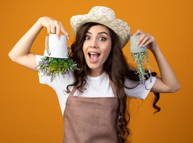 Jovem jardineira surpresa de uniforme, usando chapéu de jardinagem, segurando vasos de flores de cabeça para baixo