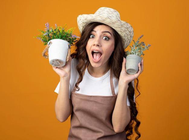 Jovem jardineira surpresa de uniforme, usando chapéu de jardinagem, segurando vasos de flores isolados na parede laranja com espaço de cópia