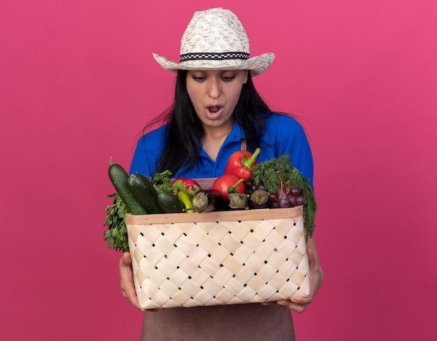 Jovem jardineira surpresa vestindo uniforme e chapéu segurando e olhando para uma cesta de vegetais isolada na parede rosa com espaço de cópia