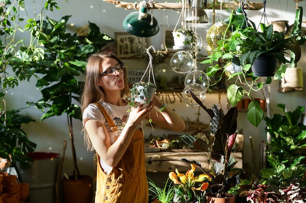 Jovem jardineira trabalhando com plantas domésticas em loja de flores, proprietária de uma pequena loja de flores