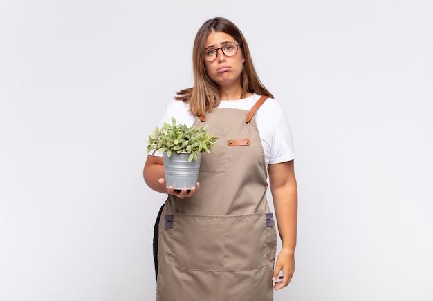 Jovem jardineira triste e resmungona com uma expressão infeliz, chorando com uma atitude negativa e frustrada