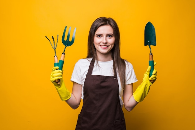 Jovem jardineira usando avental segurando um ancinho